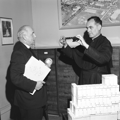 Fr. Theodore Hesburgh and Abbot Astrik Gabriel look at the first microfilm to arrive from the Biblioteca Ambrosiana in May, 1963