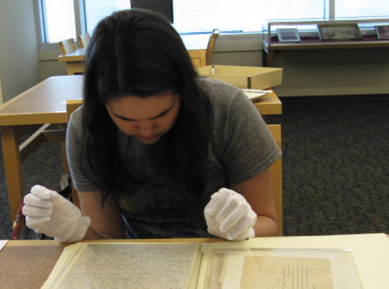 UNF student carefully handling a Special Collections item with gloves.