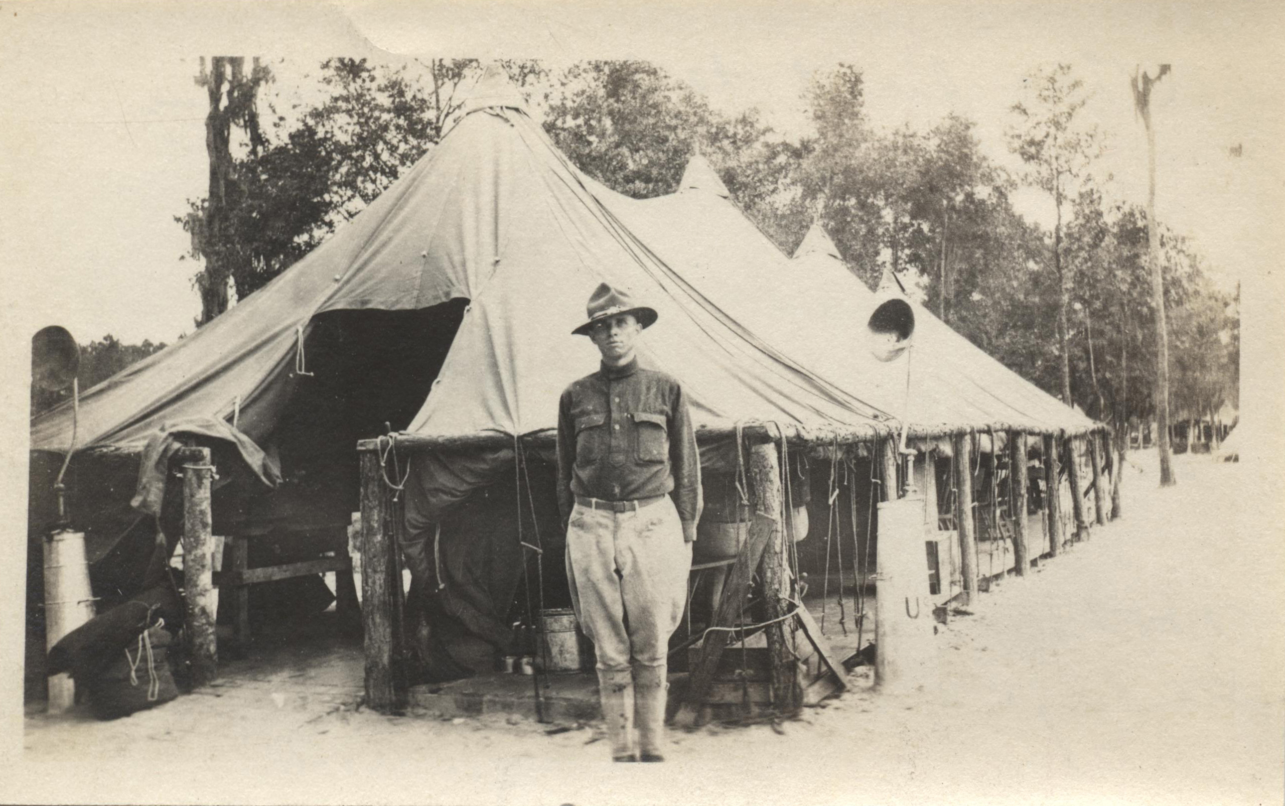 Historic photograph of a soldier standing in front of a tent.