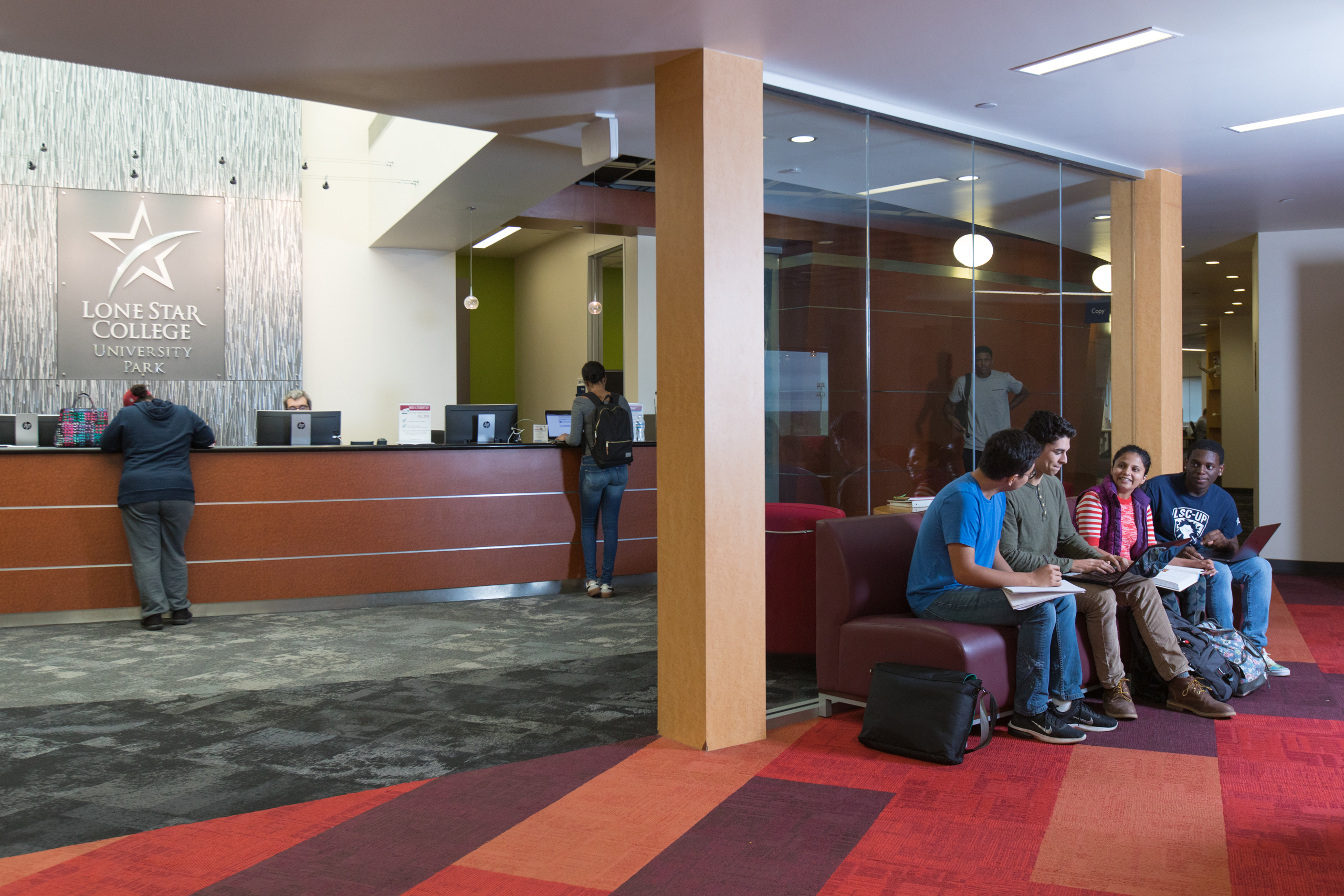 Staged photo of SLRC entry and front desk with students collaborating on the couch and a couple other students getting help at the front desk.