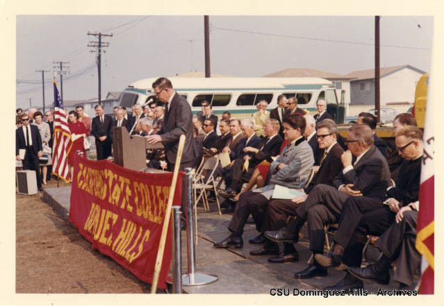 College President Leo Cain addresses crowd from podium during groundbreaking ceremony for permanent campus.  Visitors and dignitaries look on.  Cermony held on December 5, 1967.