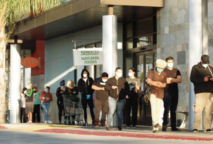 Residents of LA County in line at Sprits Natural Food store wearing face coverings and social distancing.