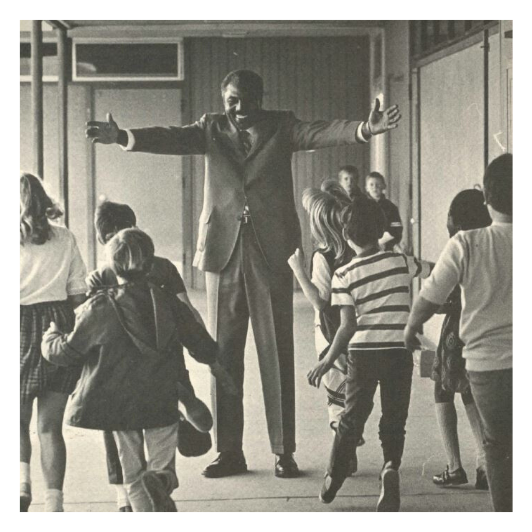 Wilson C. Riles with outstretched arms to a group of children.