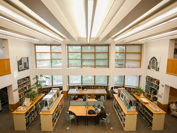 desks with people flanked by rows of bookshelves in front of windows at the Design Library