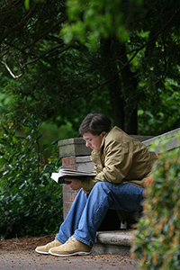 Student seated outdoors reading a book