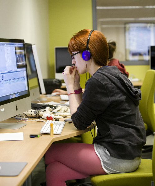 Student seated at computer wearing headphones