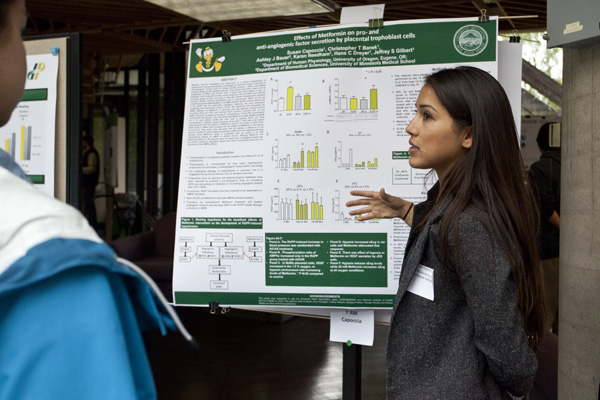 Student sharing poster at poster session