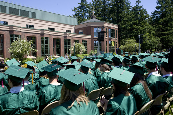 Graduating class of UO students in caps and gowns outside of Knight Library