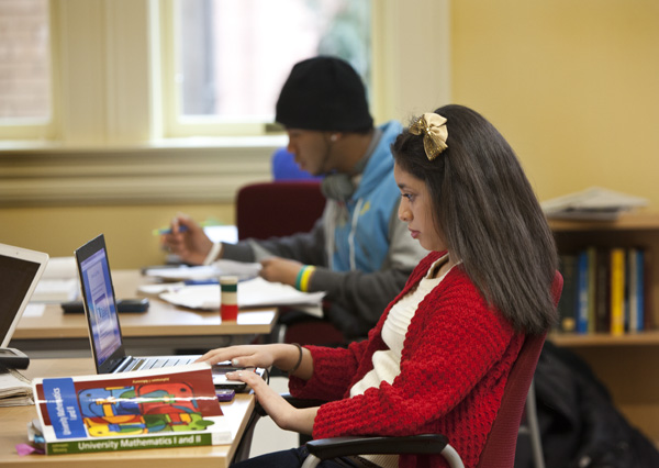 Students working at tables on laptops and notebooks on homework assignments