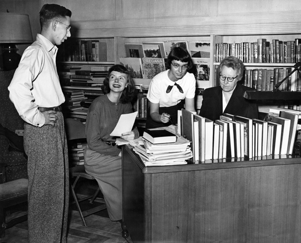 A black and white photograph group of students and archivists gathered around a desk laden with books