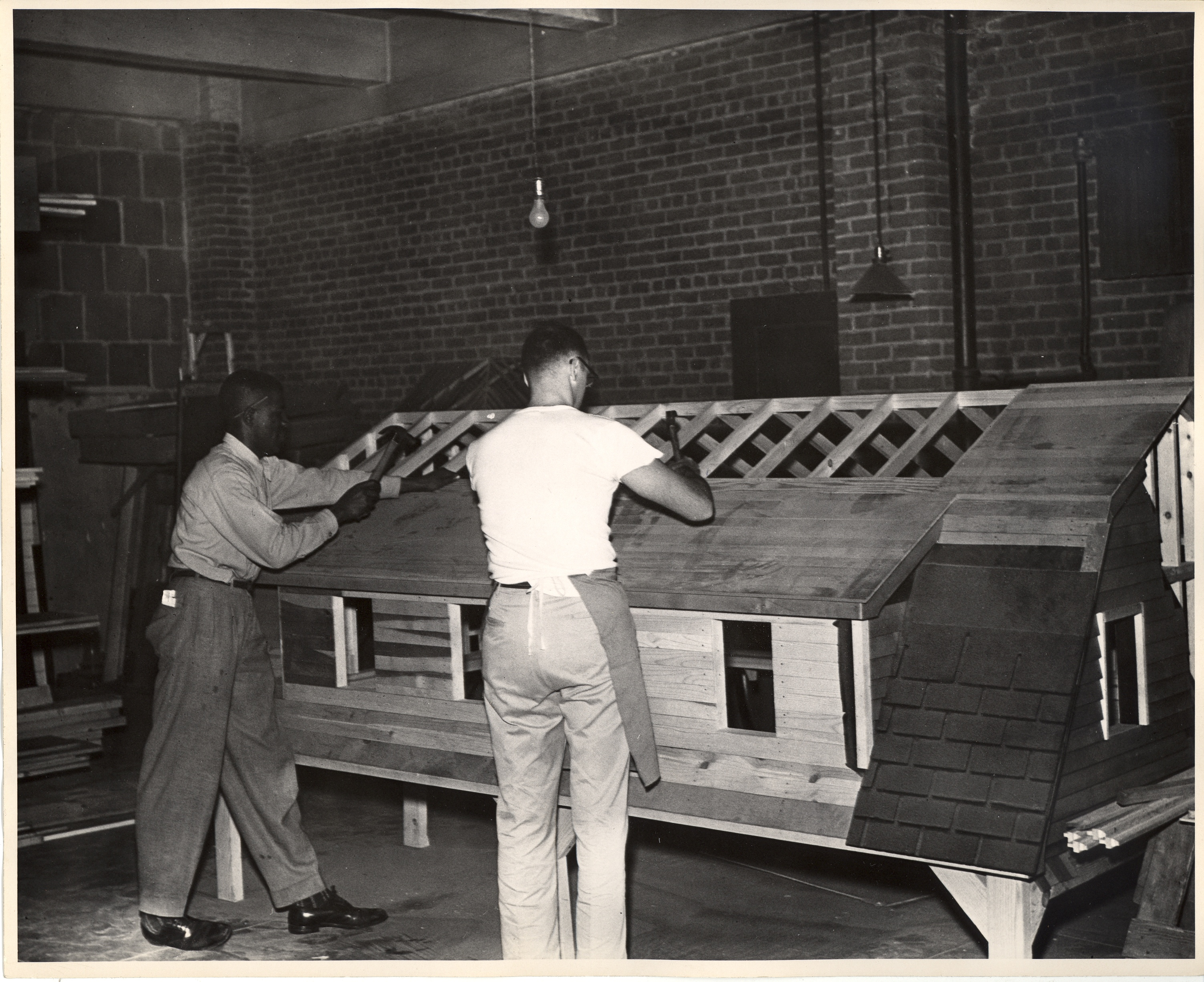 Students, likely studying carpentry, are shown working on the roof of a model of a house in a classroom at the New York Trade School.