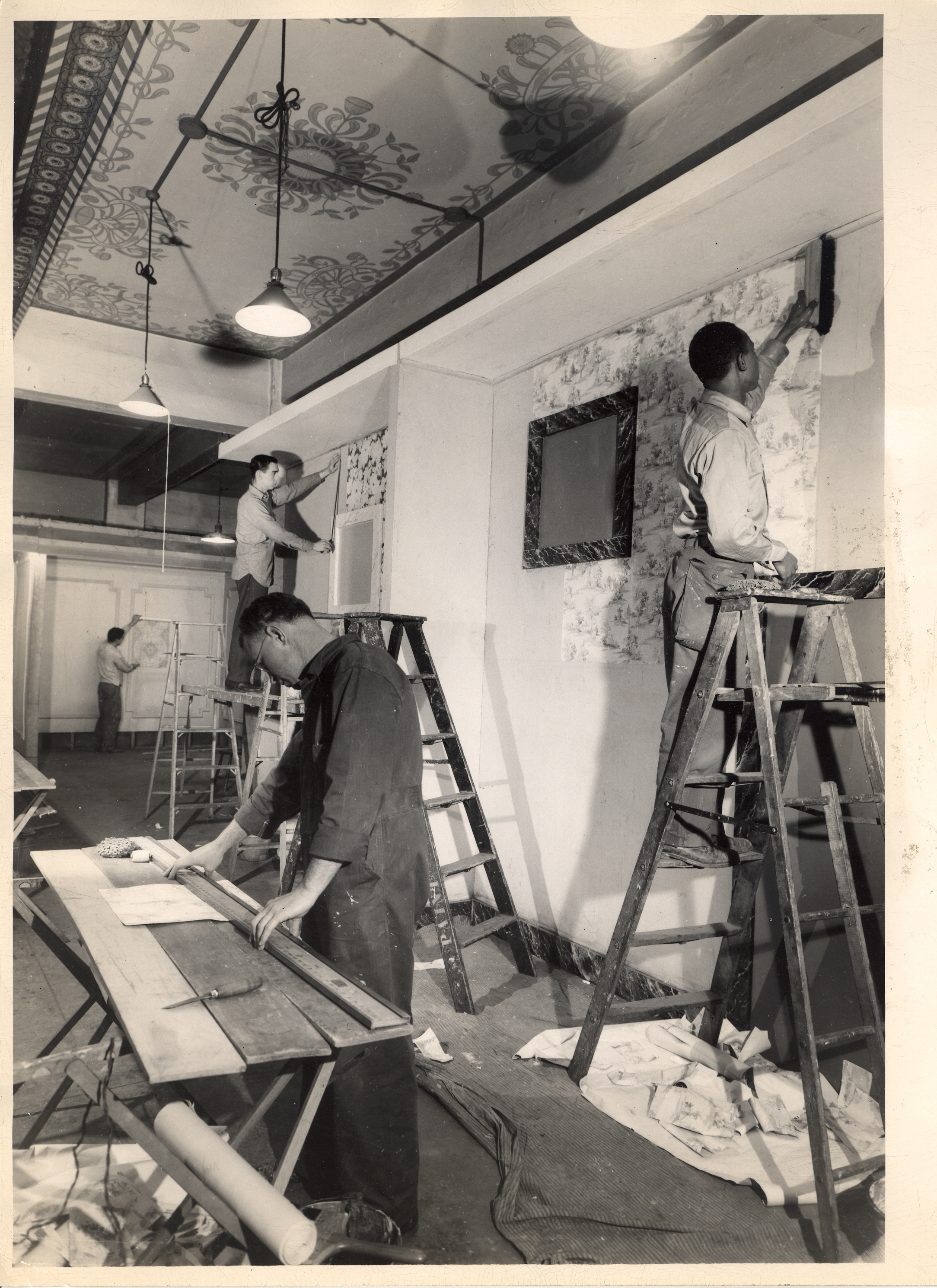 Students in the Paper Hanging Department at the New York Trade School are shown in various stages of hanging paper. Black and white photograph.