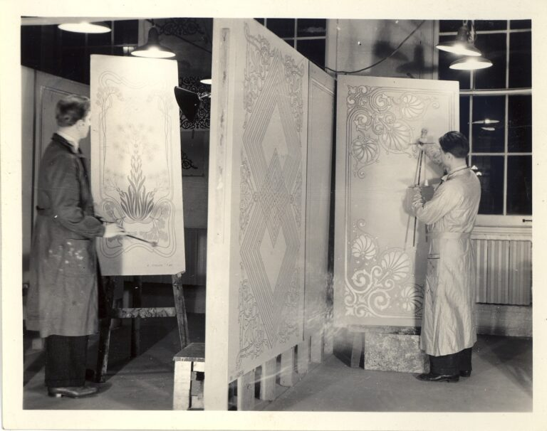 Two students learning painting at the New York Trade School are shown here working on decorative designs. Black and white photograph.