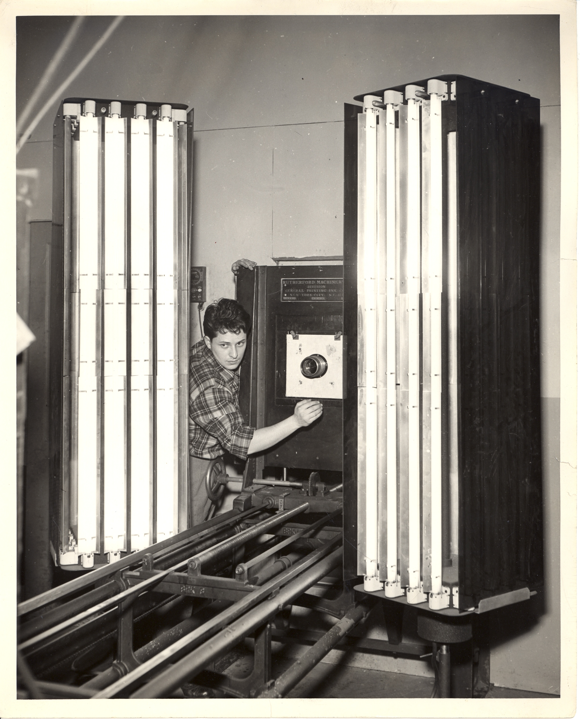 A lithography student at the New York Trade School is shown working on a machine. Black and white photograph.