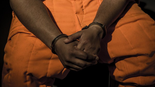 Lap of incarcerated man in orange jumpsuit, holding his hnads while handcuffed.