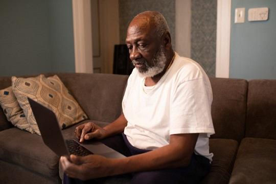 Older man using laptop at home sitting on sofa.