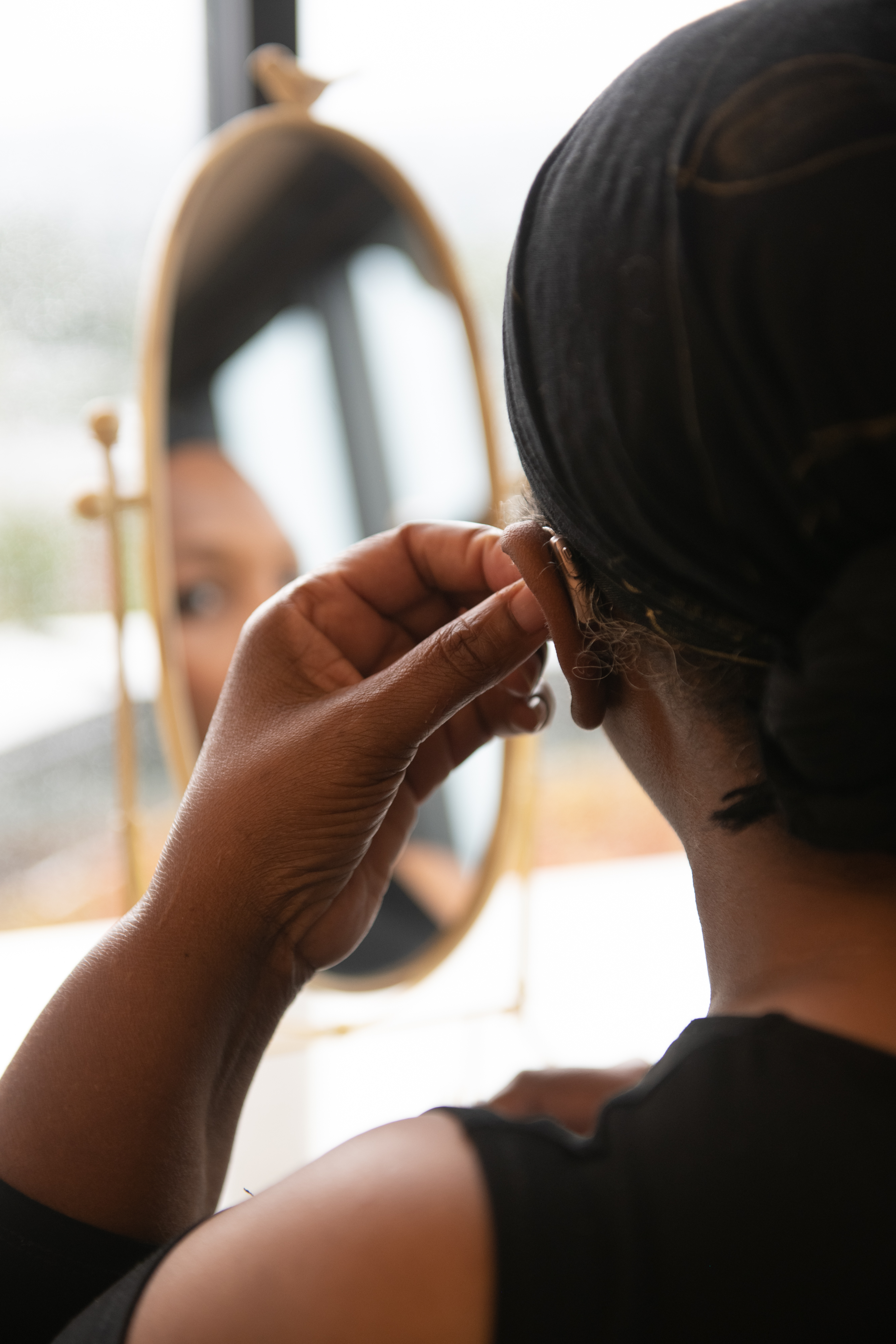 Close-up of a Black woman putting a hearing aid.