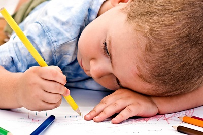 Young white child writing with pencil.