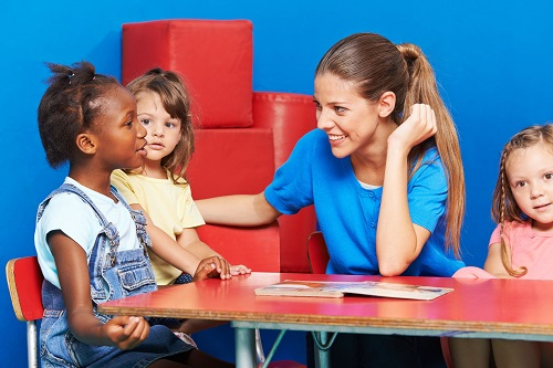 Teacher & diverse young kids sitting at table.