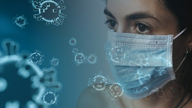 Coronavirus models super imposed over an image of a woman wearing a medical mask.