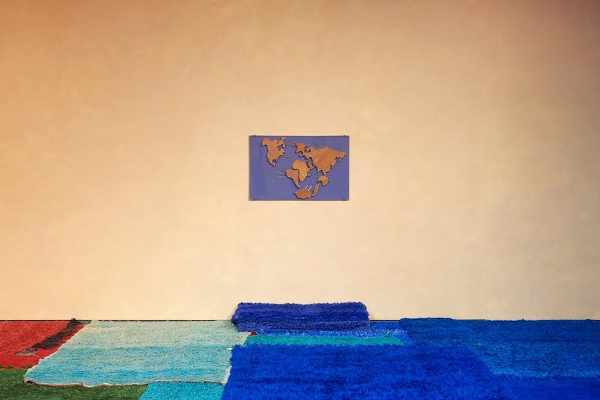 A color photo of a room with colorful carpet squares on the ground and a wooden world map on the wall.