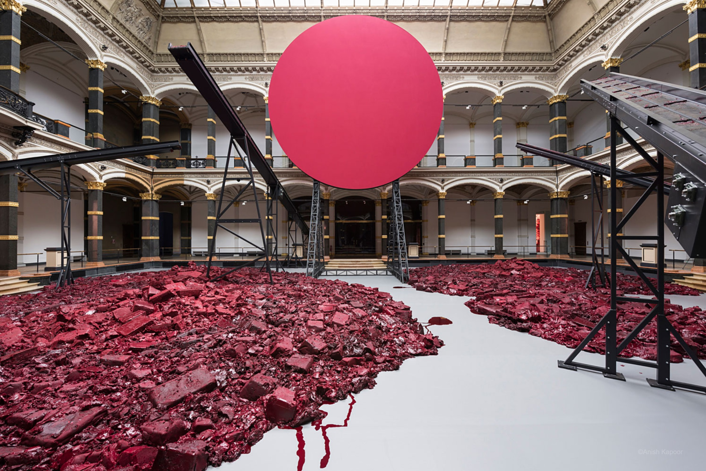 A photo of gallery space with red rubble on the ground, a suspended red sphere, and black iron bars bisecting the space.