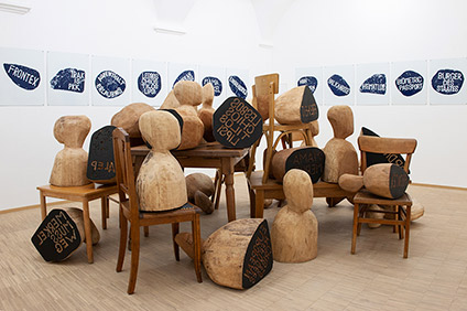A photo of a gallery space with a sculpture of chairs and carved wooden busts.