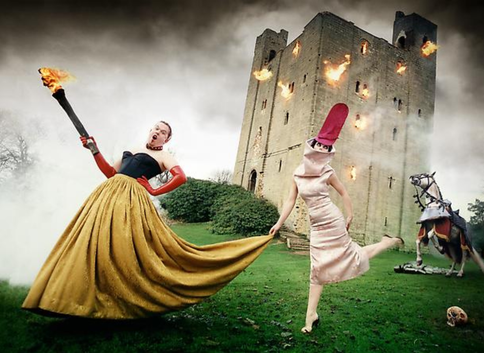 A photograph by David LaChapelle featuring Alexander McQueen and Isabella Blow in gowns in front of a burning castle.
