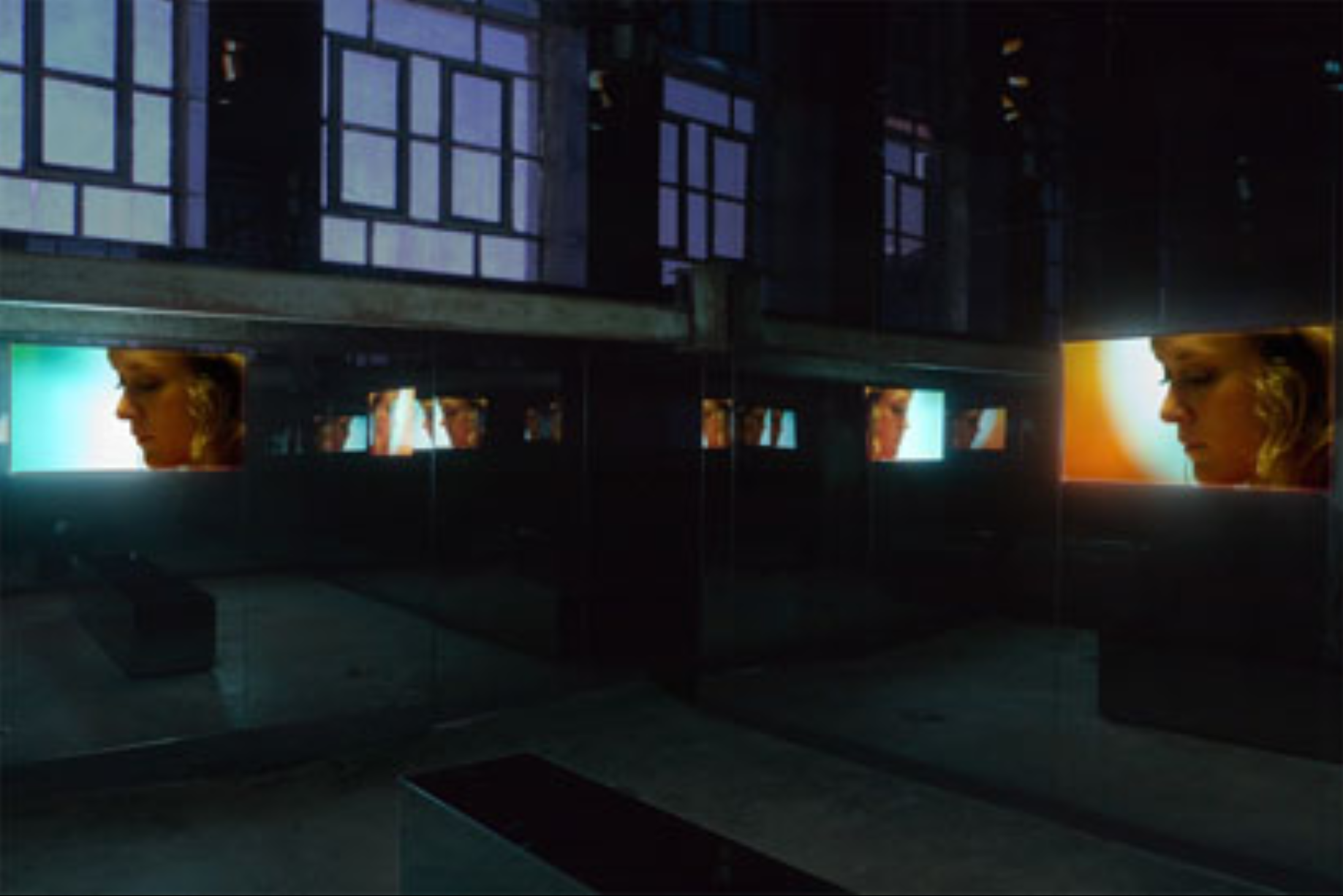 A photo of a dark gallery with multiple screens showing the same image of a white woman with blonde hair.
