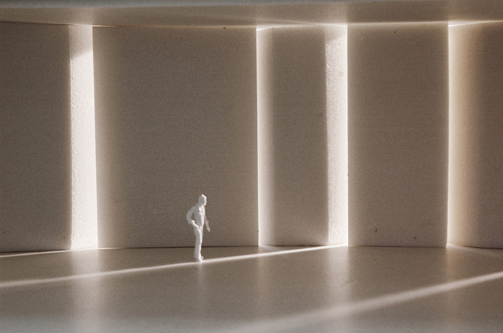 A white gallery space with vertical openings filled with light. A white human form traverses the space.