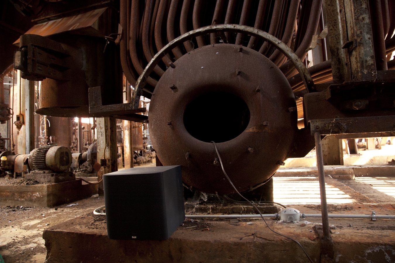 A photo of a large iron machinery with a speaker in front of it.