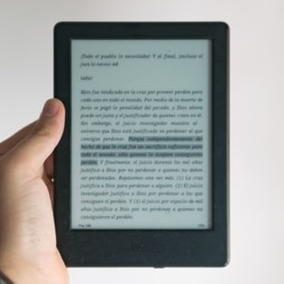 An eBook on a tablet held up in someone's hand.