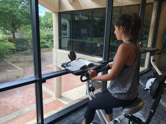 Woman riding a Fitdesk bike while reading a book