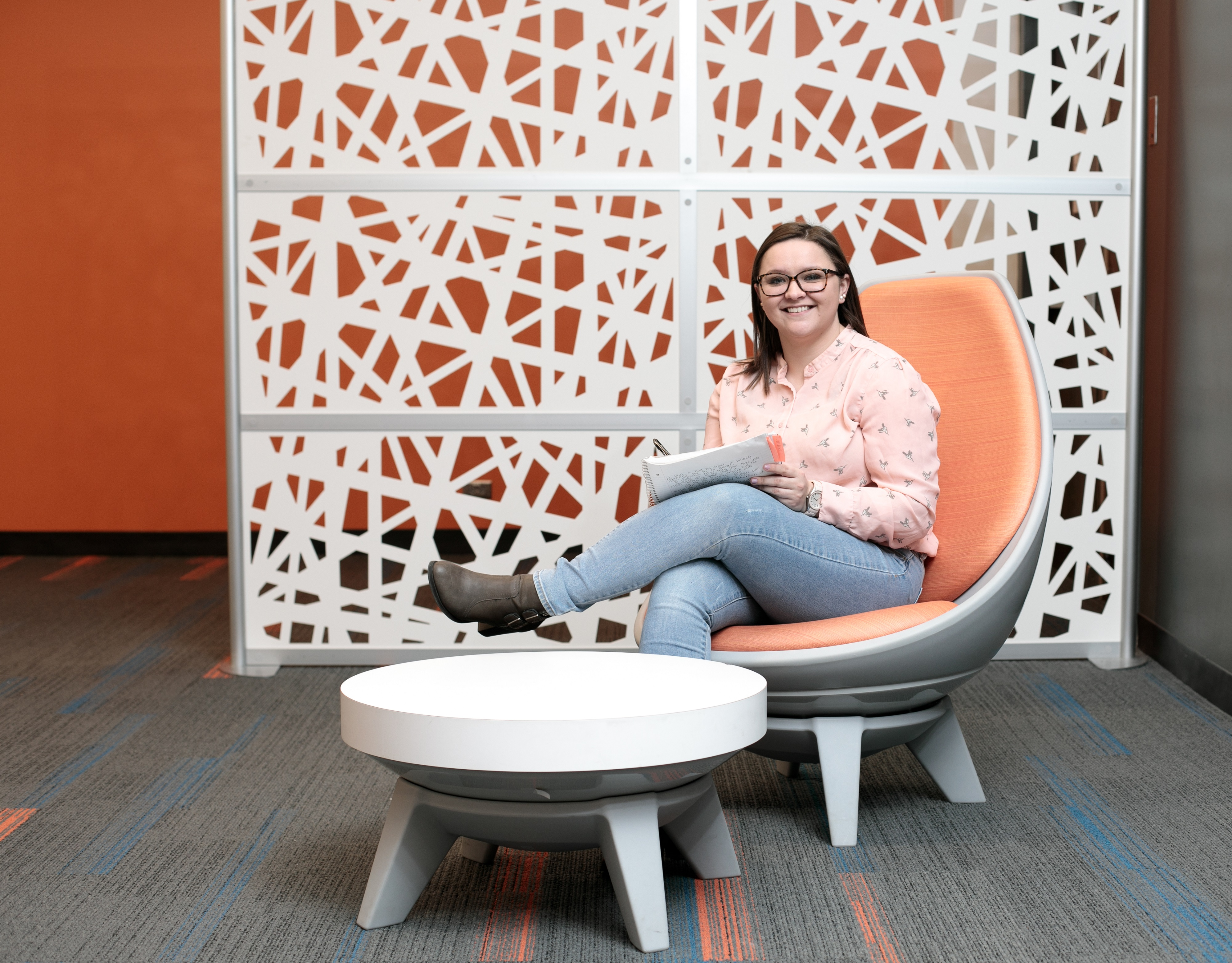 A student enjoying one of the swivel chairs on the west-side of Heterick Library.