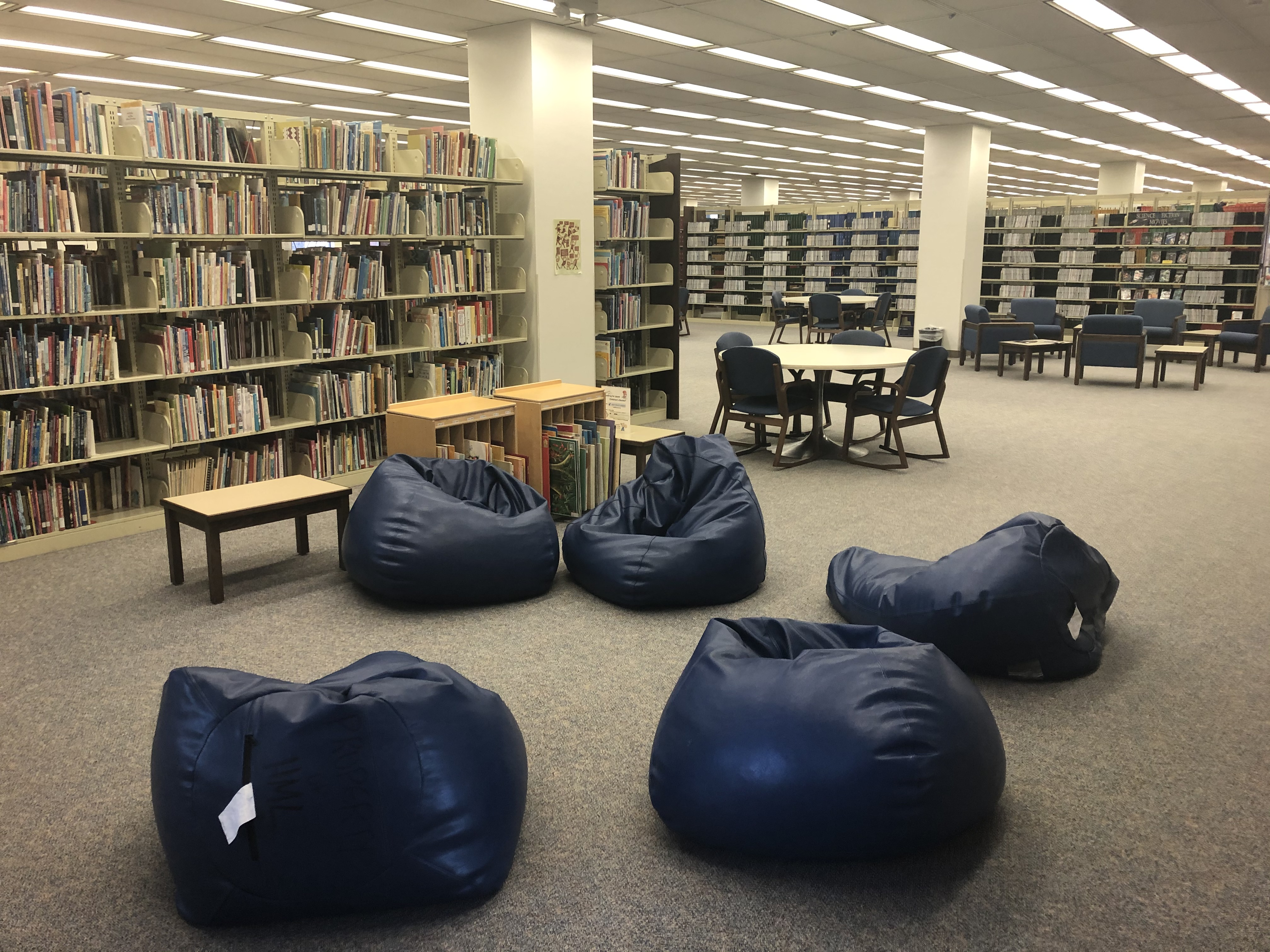 Five bean bag chairs in a circle near a shelf of library books.