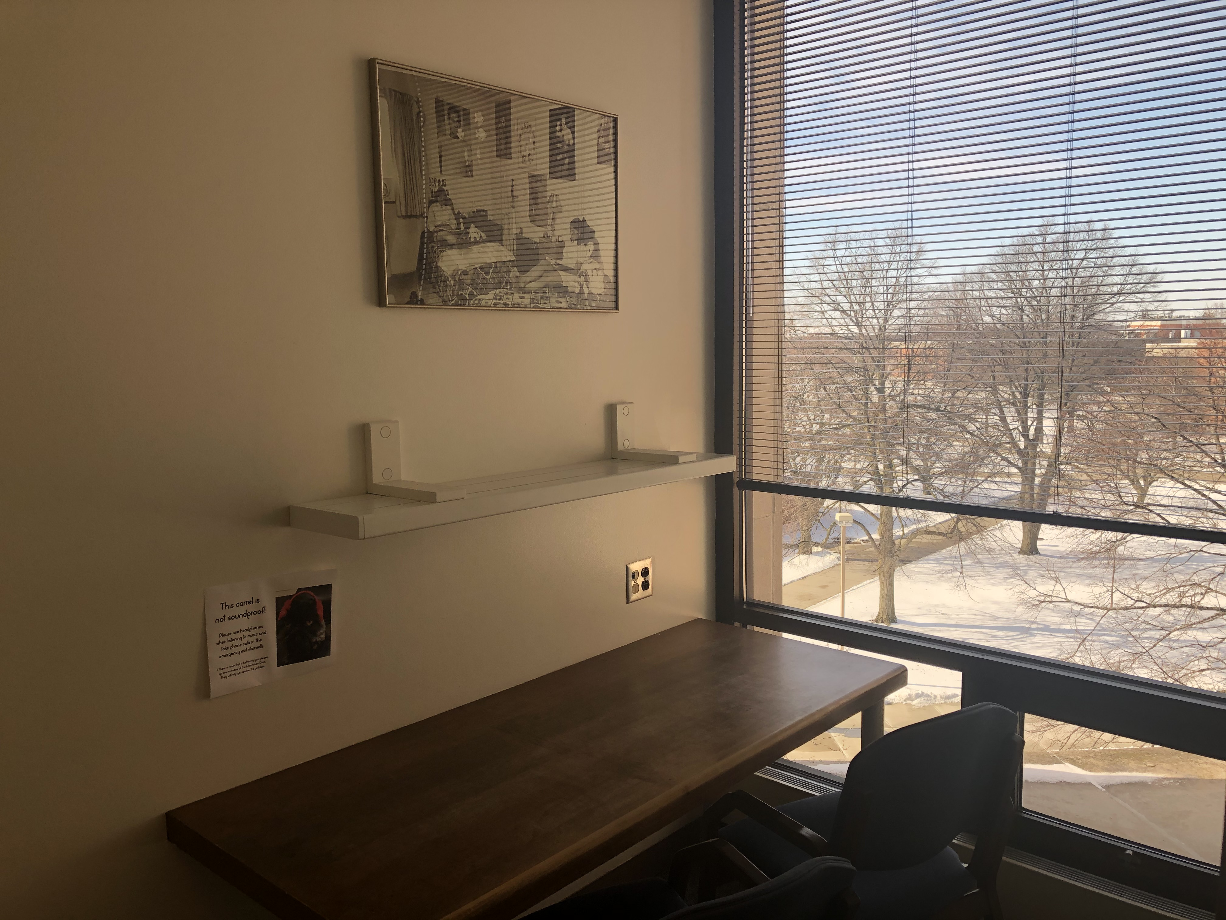An individual study space with a view of campus and accessible outlets.