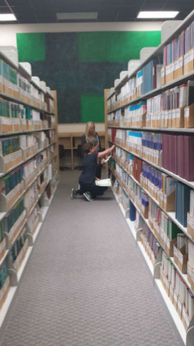 Students in the shelves,looking for a print journal