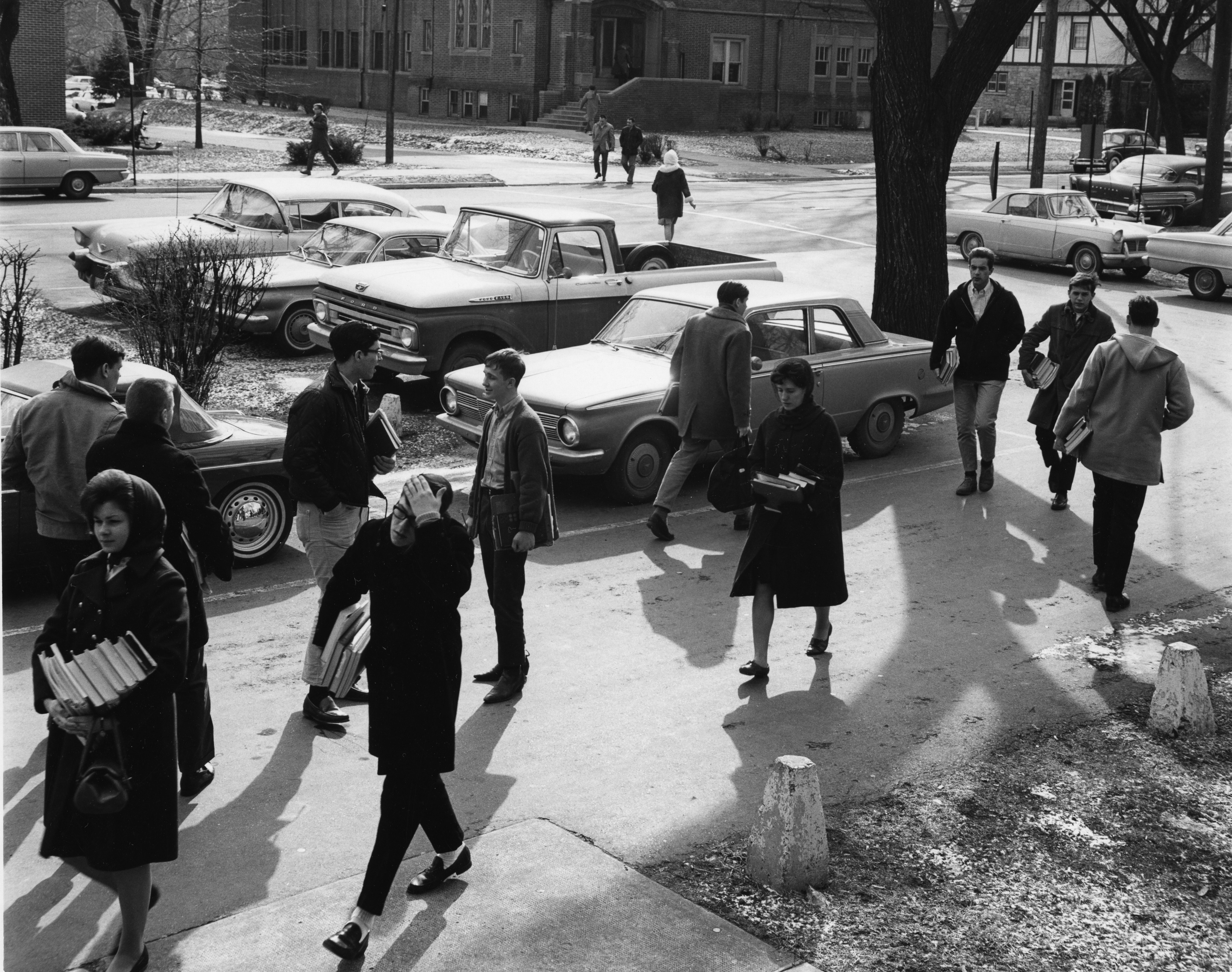 students with books walking to class outside
