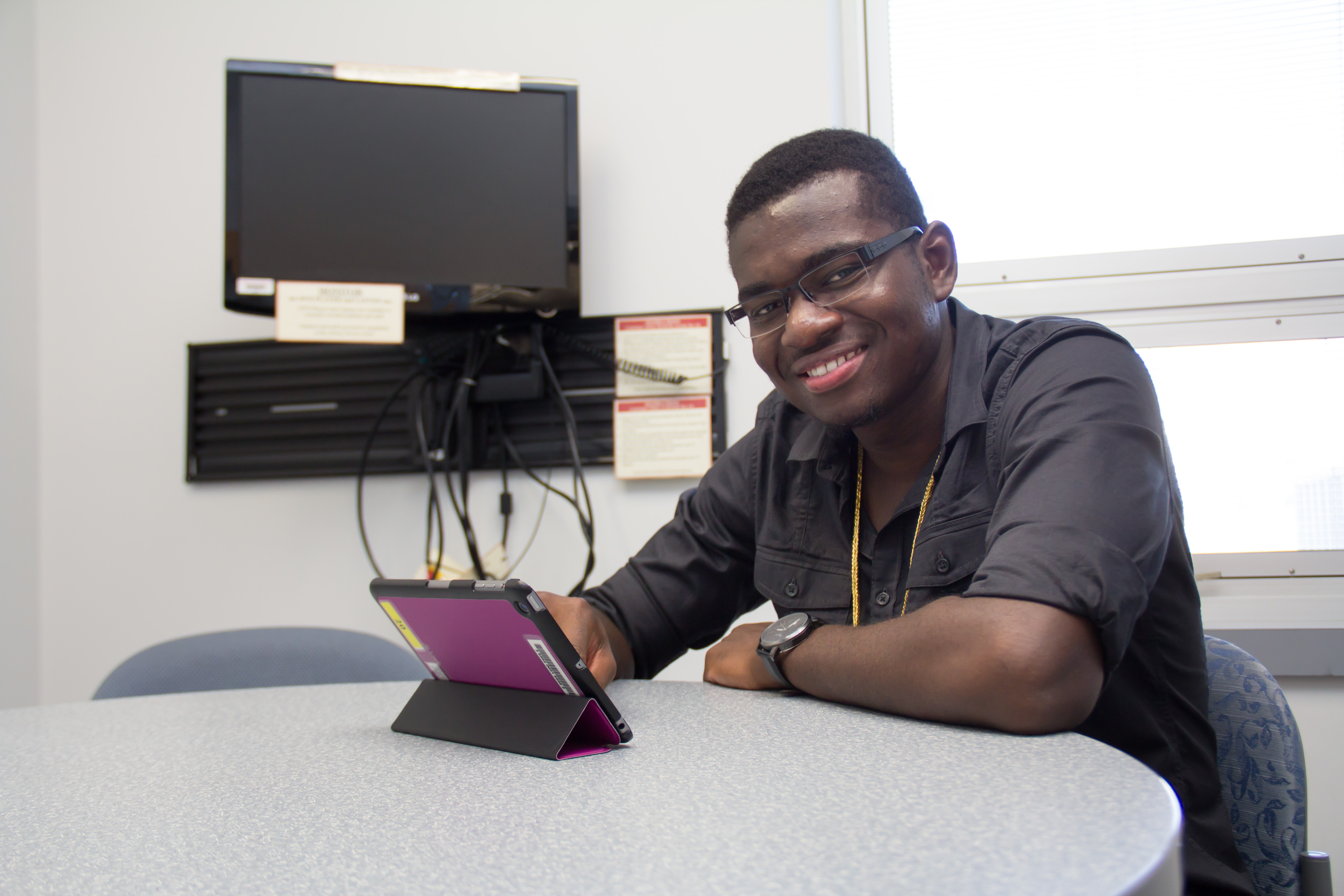 student with iPad in study room