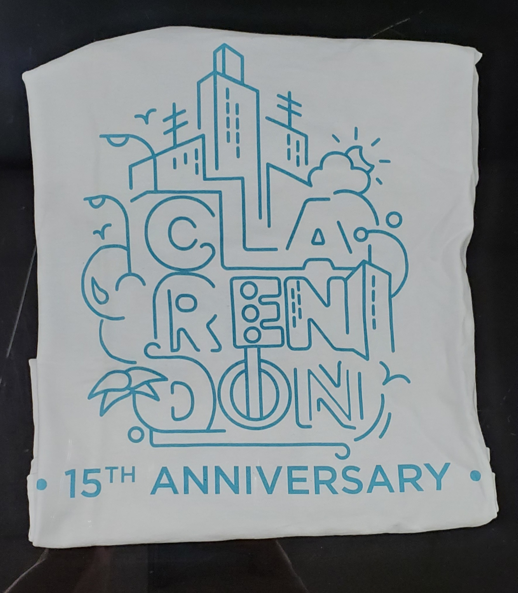 White t-shirt with blue outlined block letters spelling out Clarendon. 15th Anniversary is written underneath.