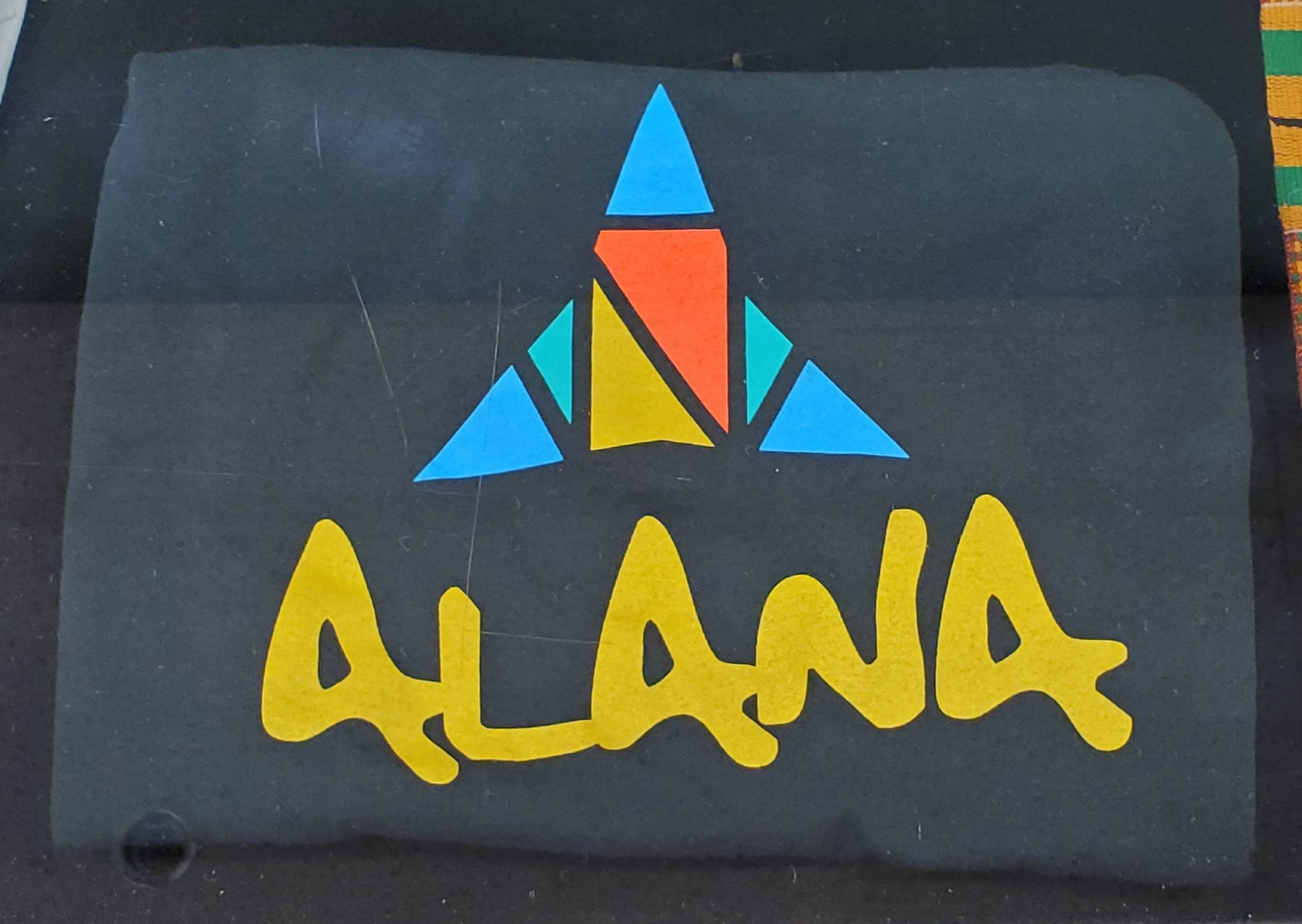 ALANA (stands for African, Latin, Asian, Native, Allies) t-shirt with the logo used for 2013-2019. The logo is triangular with a rectangle in the middle. The outer triangle parts are in blue and the two middle rectangular parts are in yellow and orange.
