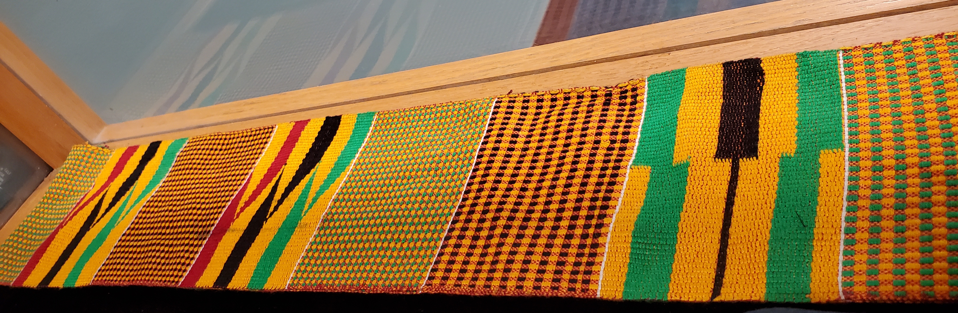 Commencement sash for students of African descent. It has different African prints in yellows, reds, greens, and blacks.