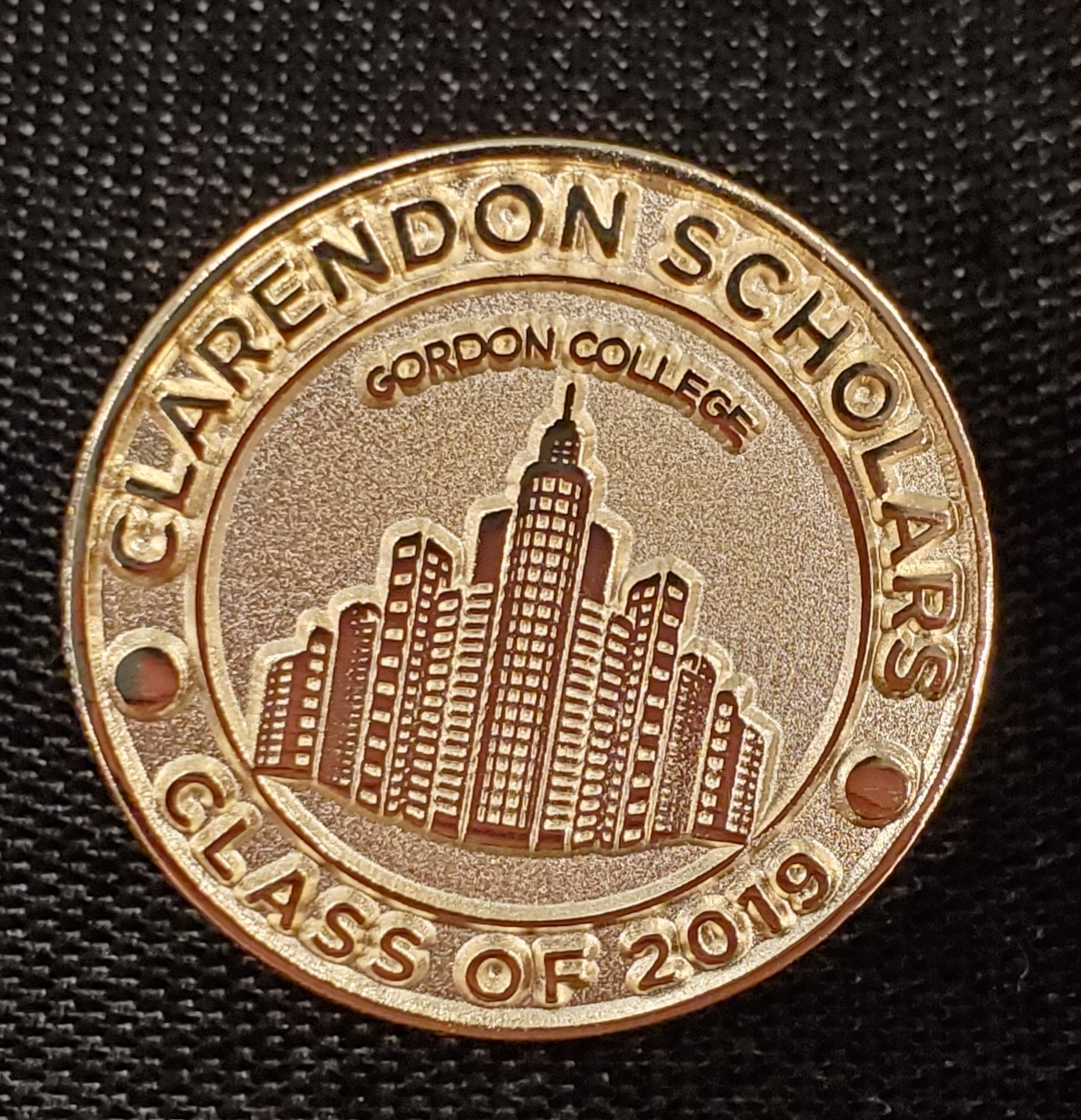 Clarendon Scholars Pin. It has a cityscape featured in the middle with