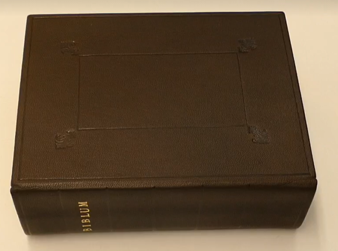 Conserved Eliot Bible. It is bound with brown leather decorated with a straight border along the edges with small, floral designs in the corners. The spine is briefly visible with