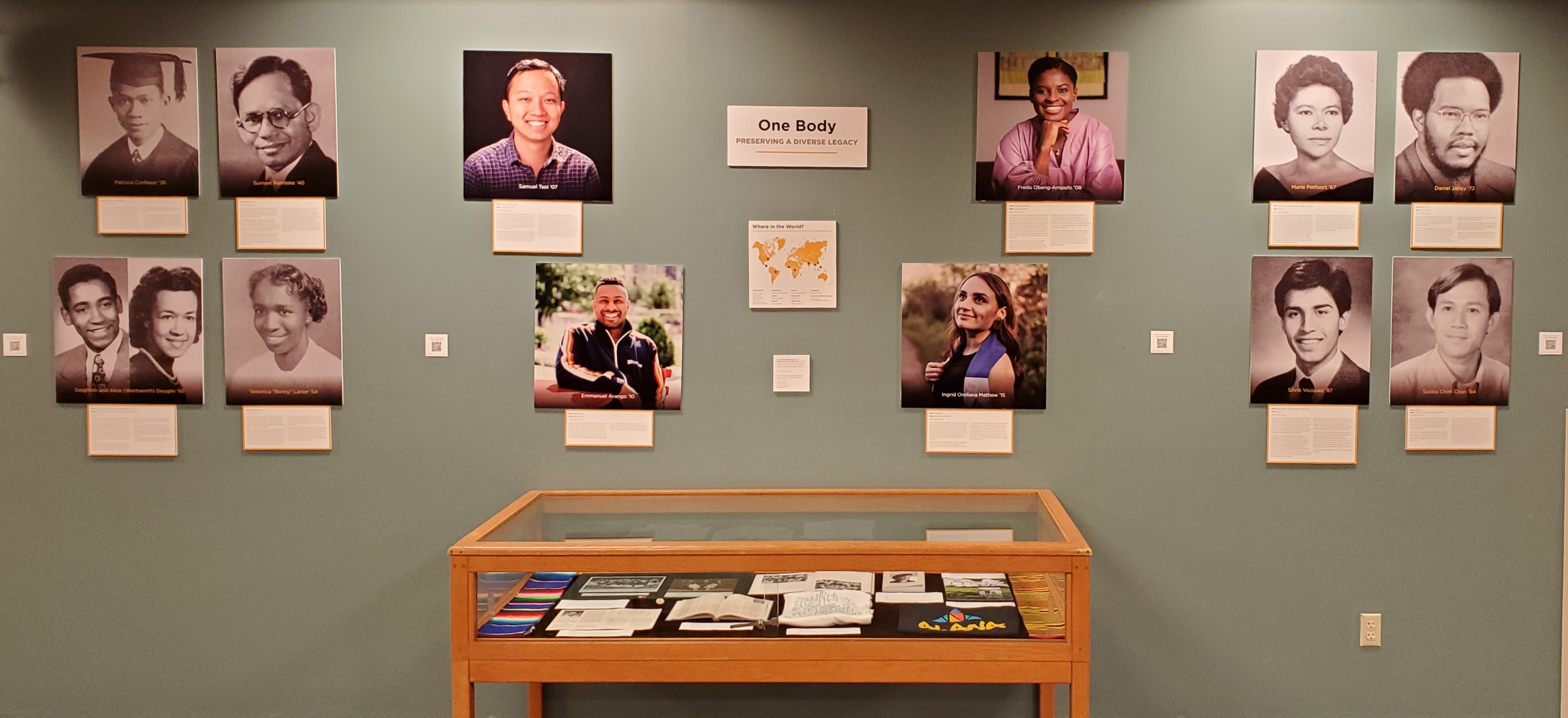 Image of the exhibit up in the Reference Room. The panels of all featured alumni are visible with four panels on either side of the wall with black and white photos and four panels in the middle with color photos of more recent alumni. Situated roughly in the center of the wall is the exhibit case with items inside barely visible.