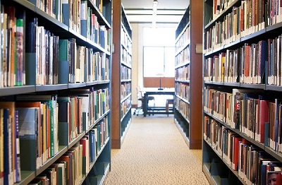 Aisle centered between two rows of library shelves filled with books