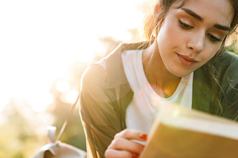 Woman reads a book in the sunlight
