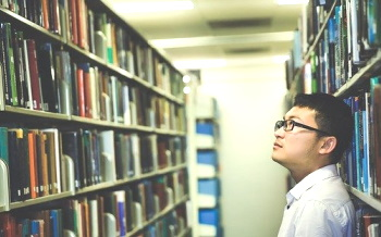 young man looks at library shelves