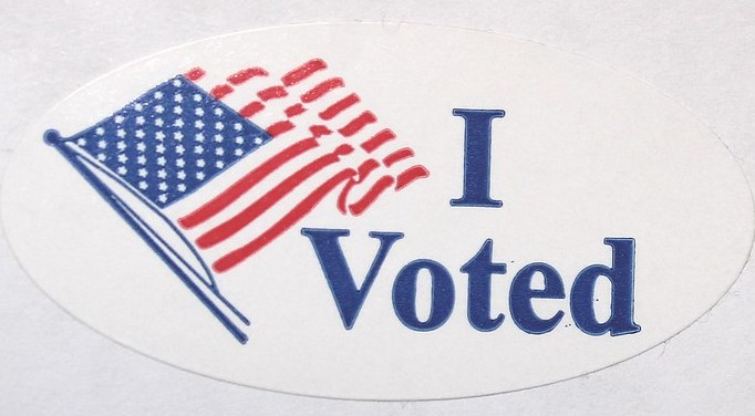 I Voted sticker with American flag.
