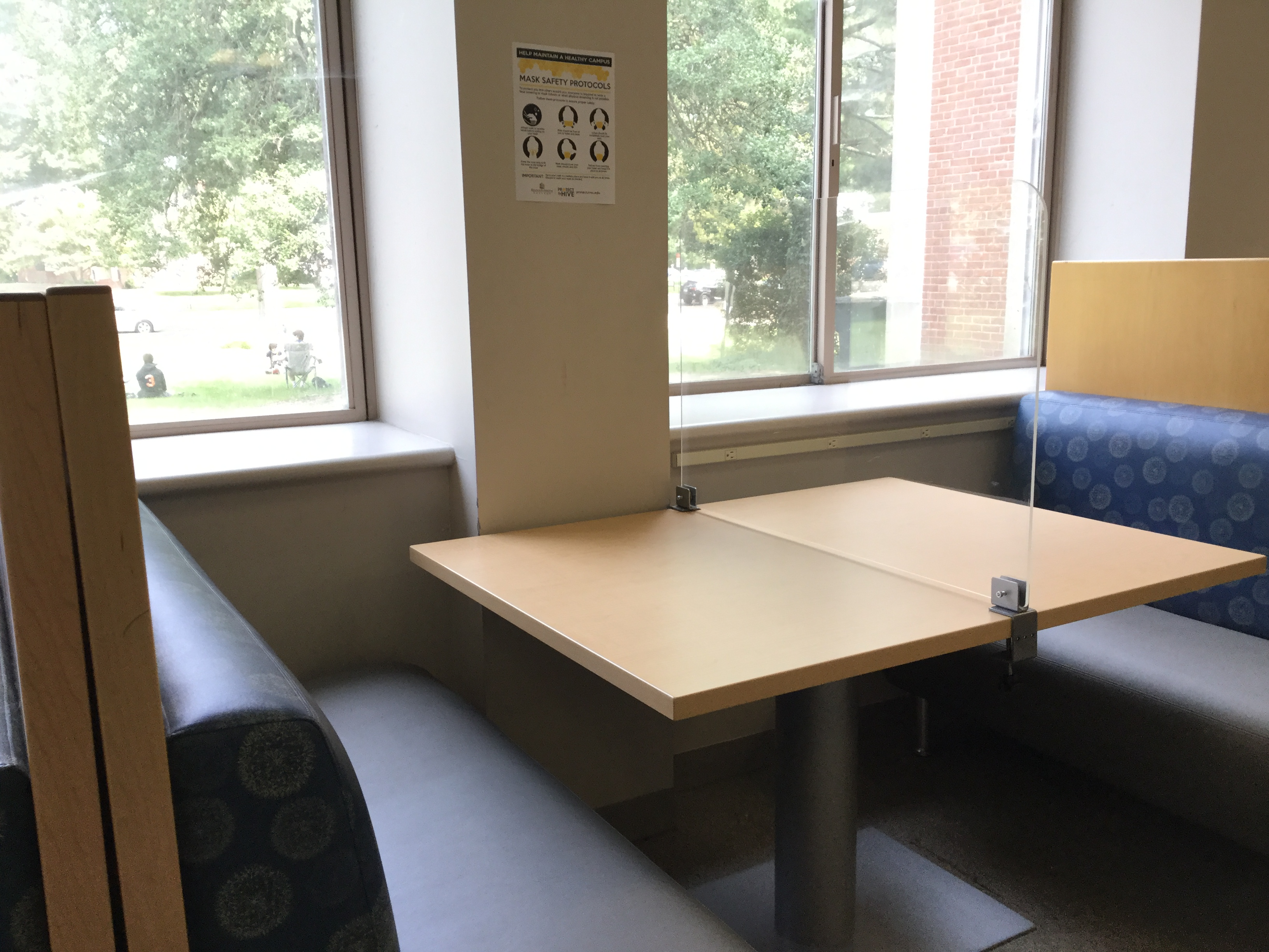 image shows booth seating in the library with plexiglass across the table.
